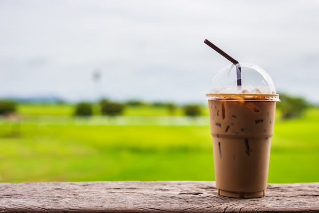 Iced coffee in plastic cup with drinking straw on terrace and green field background