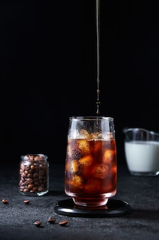 Iced coffee pouring into tall glass on dark background. concept refreshing summer drink.