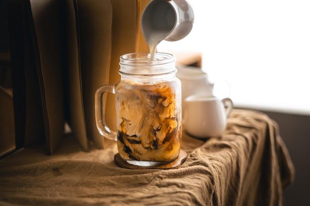 아이스 커피-커피와 함께 유리에 우유를 붓는