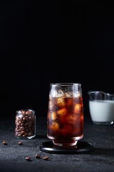 Iced coffee in tall glass on dark background. concept refreshing summer drink.