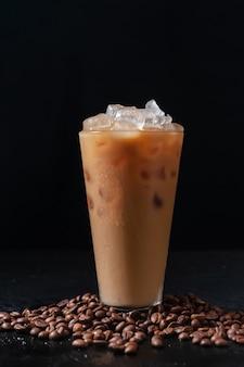 背の高いグラスに牛乳とアイスコーヒーと暗い背景にコーヒー豆