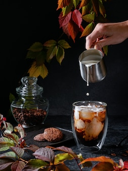 Iced coffee with cream on autumn leaves background