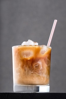 Iced coffee with cream on dark wooden table