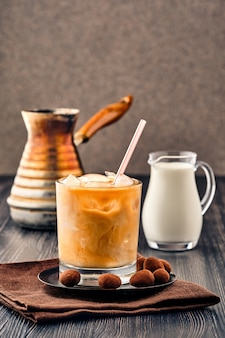 Iced coffee with cream on dark wooden wall