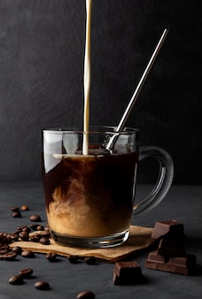 Iced coffee with cream and metal straw on a black space