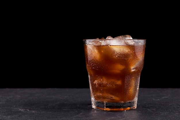 Iced coffee with ice in transparent misted glass