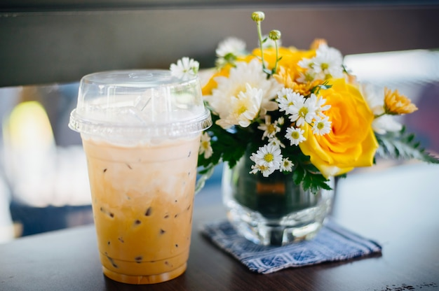 Iced coffee with iced thai tea on the table paired with flower vases