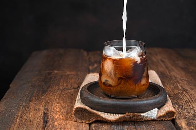 ミルク入りのアイスコーヒー、暗い壁にグラスに入った冷たい飲み物。コーヒーに牛乳を注ぐ。スペースをコピーします。