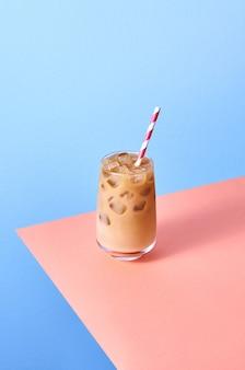 Кофе со льдом с молоком в стакане на розовом и синем фоне