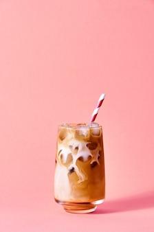 분홍색 배경에 키 큰 유리에 우유와 아이스 커피