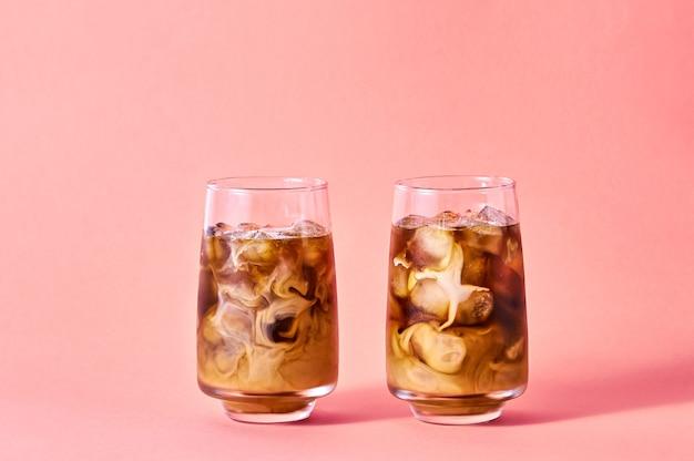Холодный кофе с молоком в высоких очках на розовом фоне