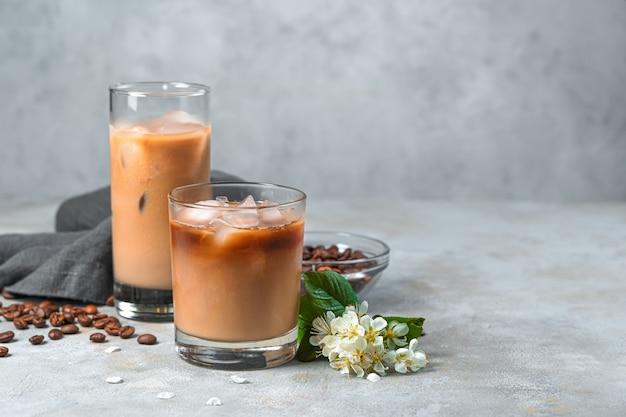 Холодный кофе с молоком на серой стене с кофейными зернами. вид сбоку, копия пространства.