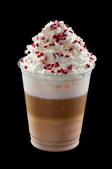 ホイップクリーム、アイスクリーム、黒の背景にプラスチックガラスのトッピングとアイスコーヒー