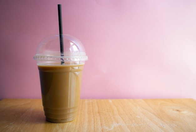 Caffè ghiacciato su una superficie di legno con una parete rosa
