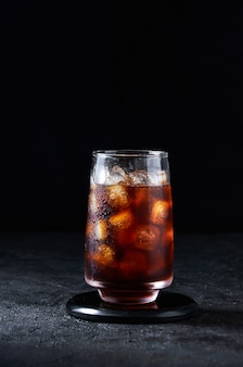 Iced cola or cold coffee in tall glass on dark background. concept refreshing summer drink.