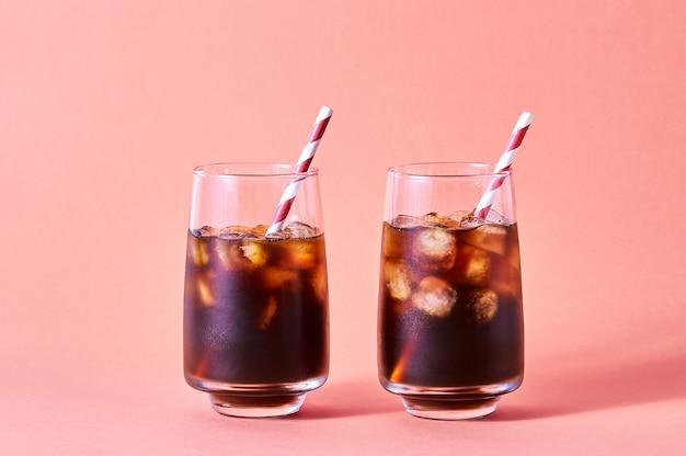 분홍색 배경에 키가 큰 안경에 아이스 콜라 또는 차가운 커피