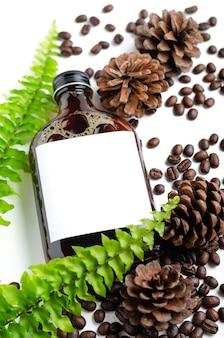 Холодный кофе со льдом в бутылке с пустой этикеткой, украшенный обжаренными кофейными зернами, сушеным конусом pind e и зеленым листом на белом фоне.
