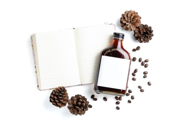흰색 공책에 빈 라벨 병에 담긴 아이스 콜드 브루 커피와 흰색 배경에 구운 커피 콩과 말린 소나무 콘으로 장식된 측면.