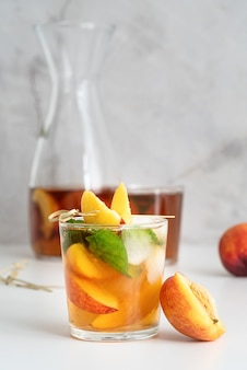 Iced cold peach tea with fruit slices and mint