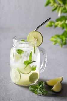 氷のように冷たい夏の自家製レモネード、灰色の背景のコピースペースにライムとミントを注入した水。