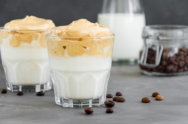아이스 달고나 커피, 어두운 배경에 유리 잔에 우유와 함께 트렌디 한 푹신한 크림 휘핑 커피.