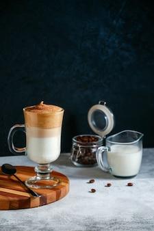 Iced dalgona coffee in a glass on dark background