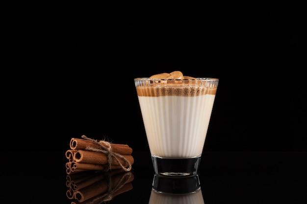 スパイスとグラスでアイスダルゴナコーヒー。トレンディなふわふわクリーミーホイップコーヒー。韓国の飲み物。