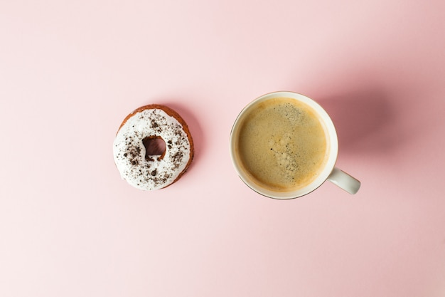 Iced donut with chocolate decor and cup of espresso on a pink pastel background