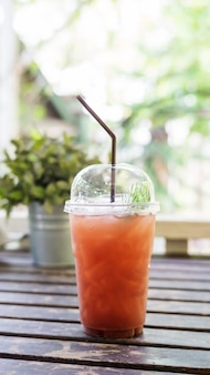 Iced fruit tea on a wooden table in a cafe.