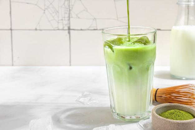 Замороженный зеленый маття латте и наливание чая в стакан на белой поверхности с жесткими тенями