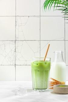 Замороженный зеленый маття латте в стакане на поверхности белой плитки с жесткими тенями и пальмовыми листьями