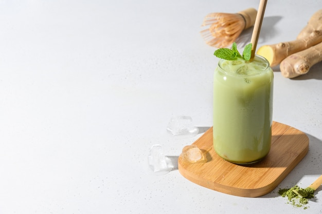Iced green matcha latte tea on white table. close up.