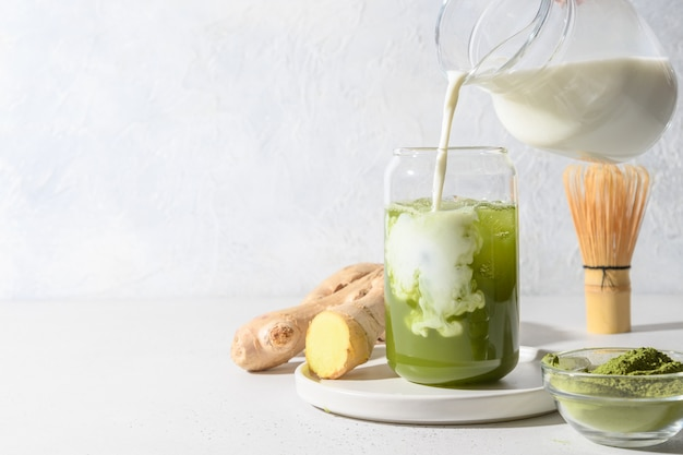 Iced green matcha tea and pouring milk in latte glass on white table. space for text. close up. horizontal orientation.