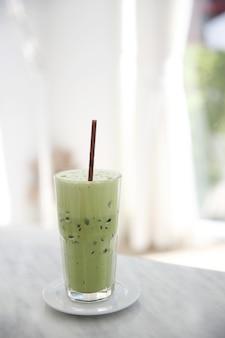 Iced green tea latte in white coffeeshop