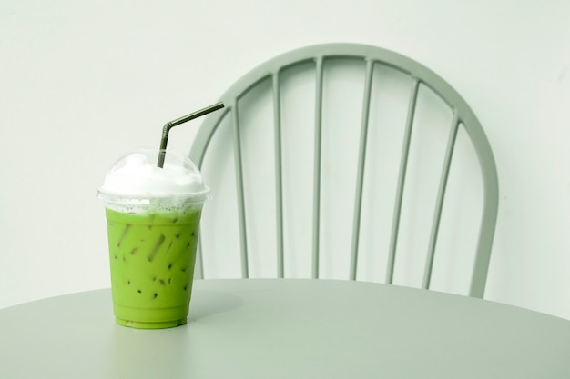 Iced green tea with straw in plastic cup on table.