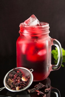 Iced hibiscus or karkade tea in the glass on the black  background. location vertical. closeup.