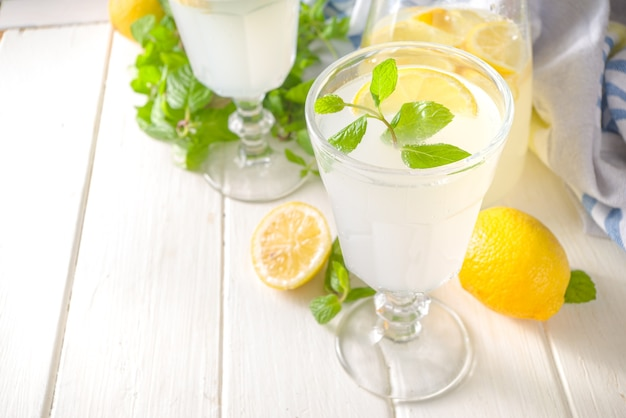 Iced homemade lemonade drink, limoncello liqueur cocktail decorated with mint and lemons on white wooden kitchen background