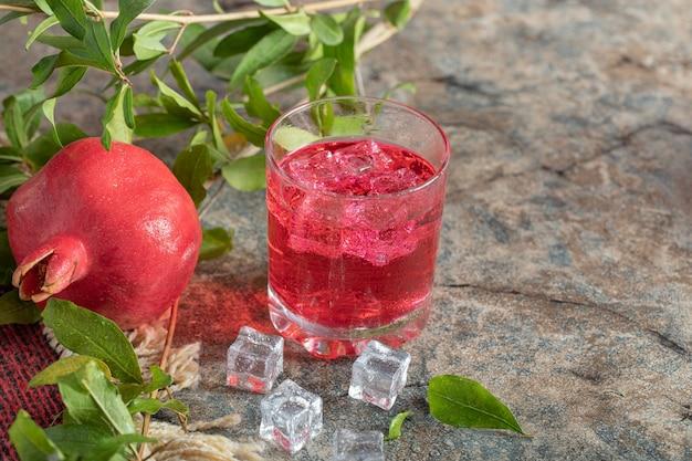 石の背景の葉とアイスジュースとザクロ