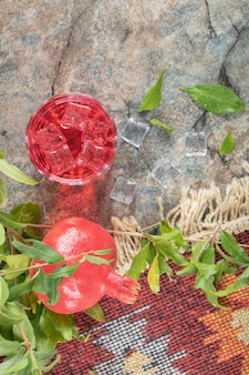 Iced juice and pomegranate with leaves on stone surface