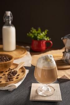 木製のテーブルの上のワイングラスの場所でホイップクリームのトッピングとチョコレートシロップを添えてアイスラテコーヒー