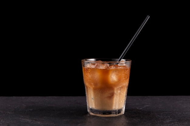 Iced latte coffee in a transparent misted glass with a straw.