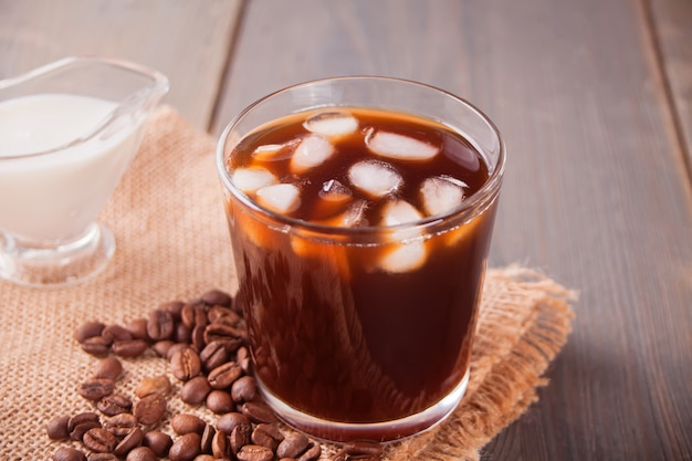 Iced latte coffee with ice cubes and coffee beans on a table.