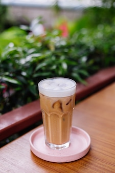 Iced latte in glass on a pink stand on wooden table in summer cafe green bushes