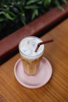 Замороженный латте в стакане на розовой подставке на деревянном столе в летнем кафе зеленые кусты
