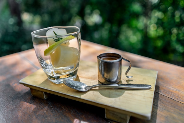 Iced lemon cube with coffee on wooden table