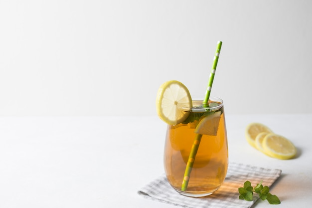 Iced lemon slices and mint leaves herbal tea on tablecloth against white background