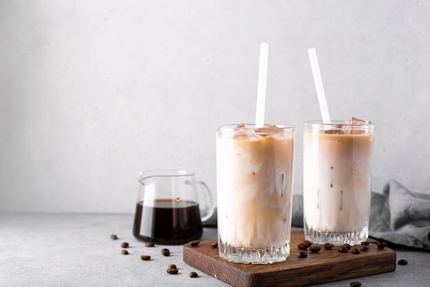 키가 큰 안경에 얼음 조각과 아이스 우유 커피를 닫습니다.