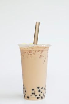 Чай со льдом и молоком в тайваньском стиле, большой пластиковый стакан с соломкой на белом фоне, свежий прохладный сладкий напиток, концепция еды и напитков