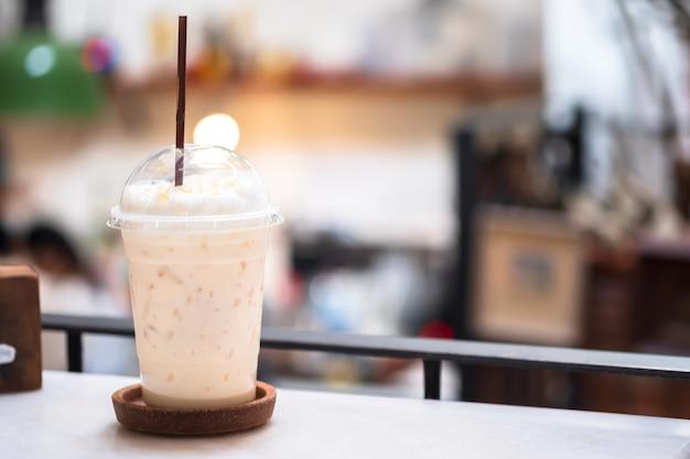 Холодный чай с молоком с медом в пластиковом стакане на размытом фоне ресторанов