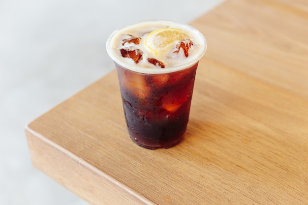 Iced nitro cold brew coffee with lemon on wooden table.